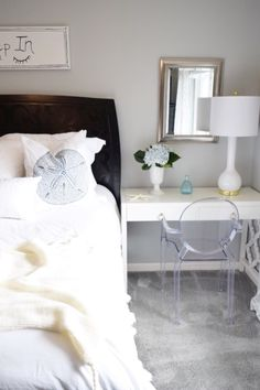 Easy Coastal Updates in the Bedroom: A sand dollar pillow, a white vase filled with blue hydrangeas, and fresh white bedding.  Available at HomeGoods. Sponsored Pin.