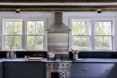 Make the most of a beautiful woodland view with windows above counters and around stove. Kitchen of the Week: Hudson Valley Farmhouse Kitchen Reborn - Remodelista Kitchen Cabinets Around Window, Rustic Kitchen Cabinets, Farmhouse Sink Kitchen, Modern Farmhouse Kitchens, Cool Kitchens, Farmhouse Signs, Farmhouse Ideas, Kitchen Floors, Colonial Kitchen