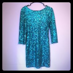 """TURQUOISE PARTY DRESS Turquoise sequin blue 3/4 sleeve mini fitted party dress bought in the UK.  CANNOT BE FOUND OR ORDERED IN USA. This was a size 12 altered to fit athletic shoulders and a 28 waist.  Model is 5'7"""" wearing 5"""" heels .  When on the back does have the scoop back look. All reasonable offers considered. Dresses Mini"""