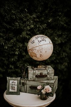 San juan capistrano outdoor rustic wedding at franciscan gardens reception decor globe with calligraphy writing and vintage suitcase decor with flowers and sign