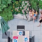 A shock of greenery surrounds the outdoor dining area of this Toronto backyard, where the family awaits a freshly-barbecued meal. Photo b...
