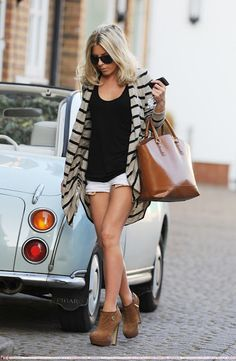Mollie King in shorts, black top, striped cardigan and brown ankle boots, accessorized with black sunglasses and Zara tote.
