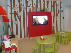 The painted trees on the TV wall cork mural represent a forest and the kids' paintings represent the fruits on the trees. The bold red shelf above the TV acts as the perfect spot to display books