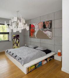 Sypialnię ze ścianą wyłożoną płytami z betonu architektonicznego ocieplono kolorowym abstrakcyjnym obrazem / The concrete wall in the bedroom can be softened with the use of strong color paintings.