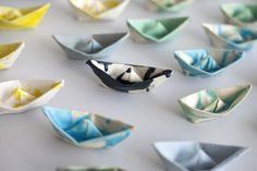 Origami paper boats are casted with ceramic paste and put in a kiln where the paper burns off leaving only a very thin layer of ceramic shell. $30