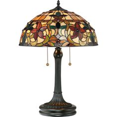 This lovely Tiffany style collection features a handcrafted genuine art glass shade created in hues of amber caramel ginger and emerald. The glass is arranged in a classic Art Nouveau pattern. The warm color palette creates a harmonious balance of light and the complementary base is finished in a vintage bronze.