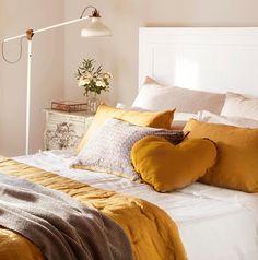 Detalle de cama con cojines y ropa de cama en tonos mostaza y gris