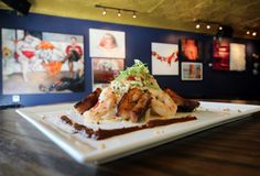 Dip into Gallery Bar's Swimming Pig, jumbo shrimp, pork belly, garlic-chile rice noodles, and mango gastrique.