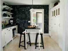 Hampton's kitchen:  blackboard wall; white cabinets/black counters; open shelves mixed with built-in pantry; light floors