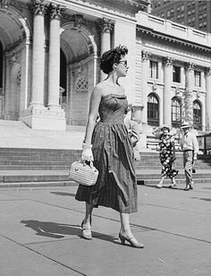 Woman on New York Street wearing a strapless sundress looking chic with short haircut, sunglasses, handbag and heeels in1949