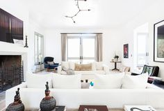 White and gorgeous living space with Sputnik light and fireplace