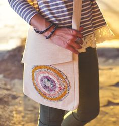 """This cotton-lined jute messenger bag is embellished with a hand crocheted patch made from up-cycled saris. Your purchase helps young women in India who have been given vocational training to earn a fair trade income and hope for a better life. Each bag is made with an array of beautiful saris, making each one unique!  Assorted colors. 12""""X14"""". 22"""" strap from shoulder to seam."""