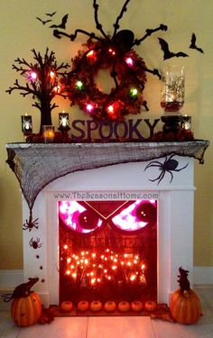 Halloween decorations - face in the fireplace with spiders and lit up mantlescape.
