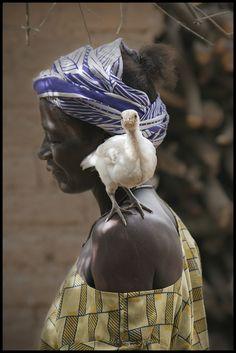 A chicken balances itself on a woman's shoulder. Burkina Faso.