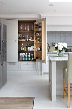 : Transitional Kitchen With White Wooden Pantry Cabinet To Save Assorted Drinks On Shelves Inside It On White Tiled Floor