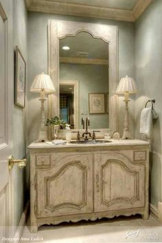 I love everything about this bathroom...from the soft subtle color on the walls to the distressed cabinet and lamps!