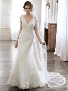 Maggie Sottero - PILAR, Completely timeless is this slim A-line wedding dress. Constructed of delicate lace and ethereal tulle, this gown features scalloped trim adorning the V-neckline and plunging back. Complete with dainty lace sleeves. Finished with covered button over zipper back closure.