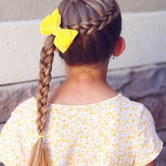 Simple wrapped around French Dutch braid. I like to secure it with an elastic once I get to the side of her head, then braid the ponytail. It stays put a lot longer when I do that. •• bow by @labellebaby ••