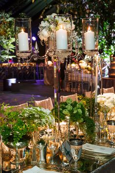 When placed next to tall candelabras, taper candles in glass hurricanes add impressive dimension.