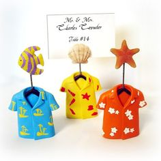 "These adorable Hawaiian shirt placecard holders are the perfect way to display your wedding place cards. They will also make a perfect favor for your guests to display their vacation photos once they get home. Each place card holder is made of poly resin and comes in 3 assorted colors and designs. Blue shirt with fish, yellow with shell and red with starfish. Each place card holder measures 2"" x 4"" and holds a 2"" x 3"" placecard or photo.  #weddingfavor #placecard #summer #beach #hawaii"