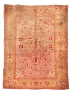 USHAK CARPET  WEST ANATOLIA, CIRCA 1900  The shaded light pink field scattered with floral motifs around a cusped ivory medallion with pendants containing similar motifs, the spandrels similar, in a broad lemon-yellow border of meandering arabesques linking palmettes between lemon-yellow flowerhead and minor plain stripes, slightly faded at one end, spot stains 11ft.8in. x 8ft.10in. (354cm. x 258cm.)