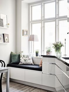 Nook in the kitchen of a Swedish apartment bathed in light. Entrance.