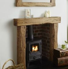 The Aged oak fire surround is styled from large solid oak beams with deep waney edges. The aged beam is hand sanded smooth on all edges before flaming the grain and hand finishing with a clear wax. Cottage Fireplace, Small Fireplace, Home Fireplace, Fireplace Remodel, Living Room With Fireplace, Fireplace Design, Fireplace Ideas, Wood Fireplace Surrounds, Wood Burner Fireplace