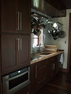 DREAM kitchen! Butcher block countertops, dark brown (cherry/mahogany wood) cabinetry, black/stainless appliances, etc. but with stone/cement sealed flooring.