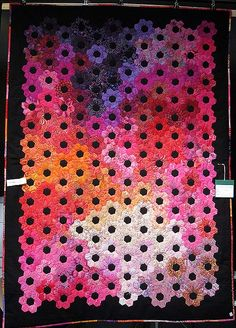 beautiful quilt using Hexagon Flowers in flaming batics.