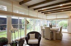 Soulad přírodních tónů vytváří kombinace různých druhů dřeva, ratanu a textilií v krémové barvě. Přiznané dřevěné stropní trámy připomínají venkovský styl.