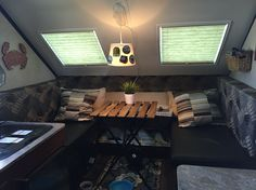 A-frame camper mod - replace the stock table with a smaller cafe table. Add an overhead light using a corded light and lampshade.