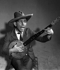 England British actor and comedian Norman Wisdom is pictured playing the banjo
