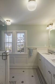 Bathroom remodel - black and white tile floor, wainscoting, double vanity sink, carrara marble counter top