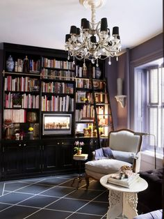 "Designer David Kaihoi built this floor-to-ceiling bookcase himself and painted it high-gloss Black by Fine Paints of Europe. The floor, painted to mimic a rug, is Hale Navy and White Down, both by Benjamin Moore. ""Big furniture makes a small room seem grander,"" says Kaihoi."