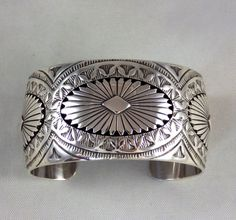 "Territorial Indian Arts  Navajo Indian silver jewelry, contemporary but in the old style.  Beautifully filed and tooled with a cold chisel, this 1 1/4"" wide silver cuff has three medallions like conchas created with another layer of silver."