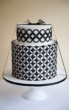Ultramodern black-and-white cake by Rouvelee's Creations, located near Melbourne, Australia. Cake designer Rouvelee Ilagan covered the confection in smooth white fondant and then embellished each tier by hand with black fondant cutouts... A black satin bow was the finishing touch.