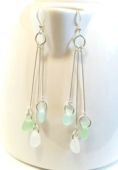 This pair of sea glass earrings is uniquely my own. They are all sterling silver. A trio of sterling silver wire is hand wrapped with lovely shades of pastel sea glass - aqua, sea foam green and white