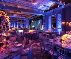 Blue perimeter lighting compliments a floral pattern that is projected throughout the wedding reception venue.