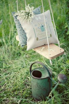 Pretty country style pillows on a garden swing next to a watering can.