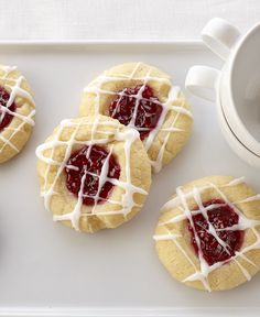 Raspberry Almond Shortbread Thumbprints from Land O'Lakes Thumbprint cookies with a buttery base, filled with raspberry preserves and drizzled with an almond glaze. These raspberry thumbprint cookies are special to serve, yet easy on your baking budget. Raspberry Thumbprint Cookies, Thumbprint Cookies Recipe, Köstliche Desserts, Delicious Desserts, Dessert Recipes, Coctails Recipes, Tea Recipes, Apple Recipes, Candy