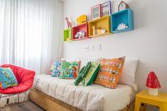 Para receber o casal de gêmeos, o quarto ganhou berço duplo amarelo, bicama com almofadas e nichos para brinquedos. Tudo sob medida pela OBA! ARQUITETURA.