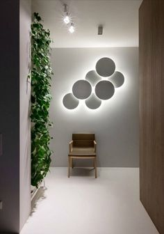A corridor with an indirect light source - an artistic light fixture composed of flat overlapping circles - mounted on the wall at the end of the corridor. On the ceiling two separate (direct light sources) spotlights lit the space. A chair also rests against the end of the corridor's wall.