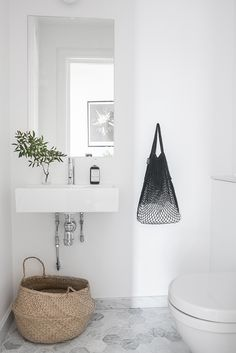 Minimalist white Scandinavian bathroom with belly basket - Top 10 tips for adding Scandinavian style to your home