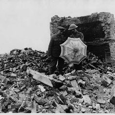Two soldiers standing in the middle of a ruined village. They are surrounded by bricks and debris. One of them holds an umbrella he has found. Behind them is a brick wall, all that remains of the building that once stood there.