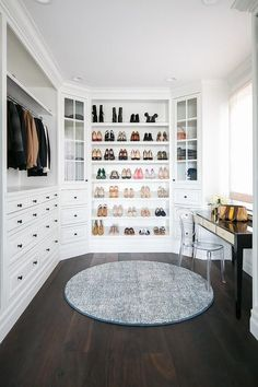 Every fashion lovers dream, this beautiful white custom closet boasts a round gray rug placed on a dark stained wood floor behind a clear acrylic vanity chair placed at a mirrored top black makeup vanity positioned under a window.
