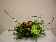 This is an Evergreen Arrangement made as an example for my Advanced Floriculture students.  I added two apples, along with Kermit Poms, Green Fugi Mums, Evergreens, Poppy Pods, Bear Grass and White Snowflake Poms.