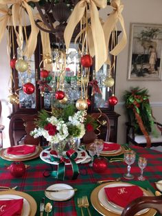 Simple curling ribbon and assorted festive ornaments hang from an ordinary chandelier. Extra large, wired edged ribbon adorns the top of the display.