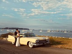 This bride and groom hopped out of their vintage auto to catch the sunset on the Eastern Prom on their wedding day in Portland, Maine.