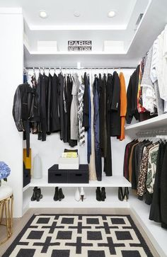 Contemporary closet features stacked clothes rails fitted with  a shoe shelf along with a white and black chain link rug layered atop a gray wash wood floor.