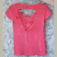 A l'origine blanc, ce tee-shirt est teint en rose et découpé dans le dos pour former des croisillons !  Retrouvez le tuto ( http://www.clonesnclowns.com/fr/2013/04/01/diy-30-jours-30-tee-shirts-13-coupe-dans-le-dos/ ) de ce tee-shirt coupé dans le dos sur le blog.
